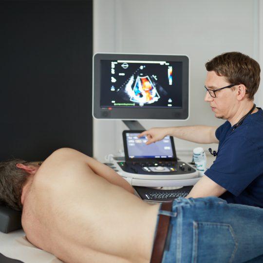 Ein Patient mit freiem Oberkörper auf der Liege, Dr. Ehrhardt sitzt daneben am Ultraschallgerät.