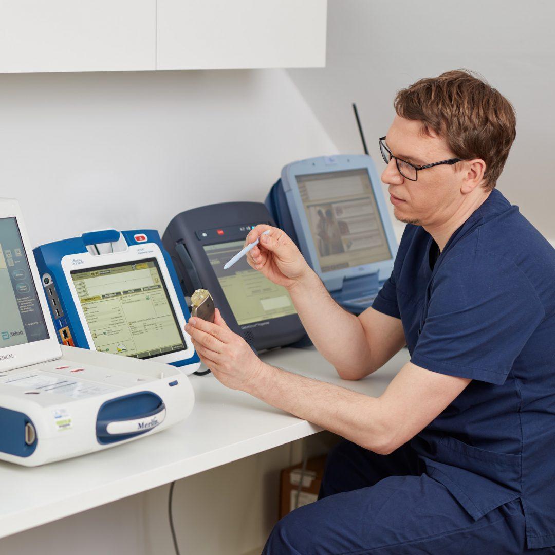 Dr. Christian Ehrhardt sitzt mit Diagnosegeräten am Tisch und kontrolliert einen Herzschrittmacher.