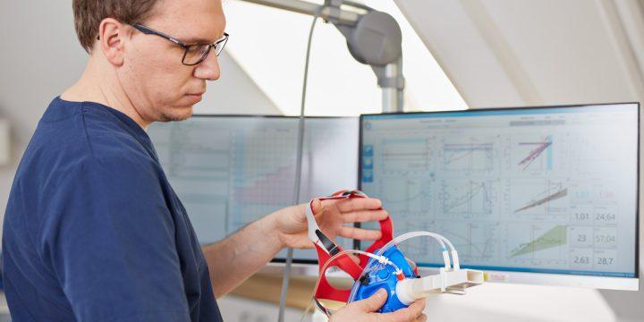 Dr. Christian Ehrhardt hält eine Atemmaske für die Spiroergometrie, im Hintergrund befinden sich mehrere Monitore.