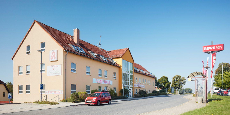 Das Ärztehaus Bischofswerda vor blauem Himmel, rechts eine Bushaltestelle